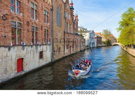 Bruges; Belgium - 11 April 2017 - Tourists enjoy their river around city tour on small tour boat on river of Bruges; Belgium on April 11; 2017