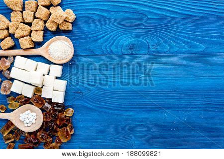 lumps of sugar in spoons on blue kitchen table background top view space for text