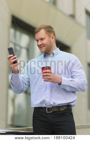 smiling businessman looking on his cell phone outdoors.
