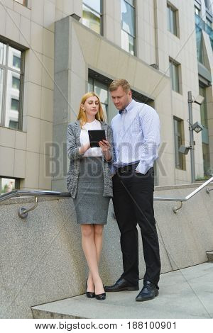 Two discontented unhappy young business people taking online meeting outdoor.