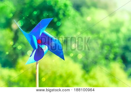 Blue paper weathercock on nature background sunlight summertime concept