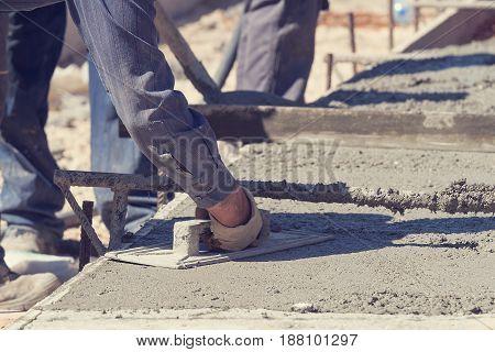 Construction worker leveling concrete pavement on site.