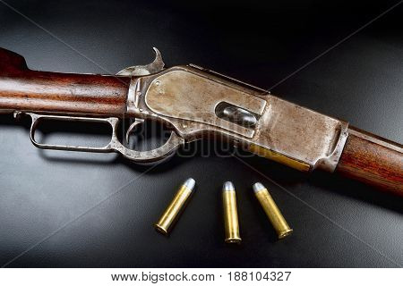 Antique 1876 Cowboy lever action rifle with 45-60 brass bullets.