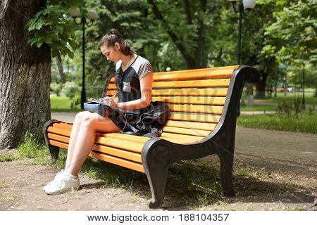 Young brunette woman studying in a park , she is sitting on a bench