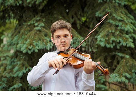 Boy playing on the violin in the park
