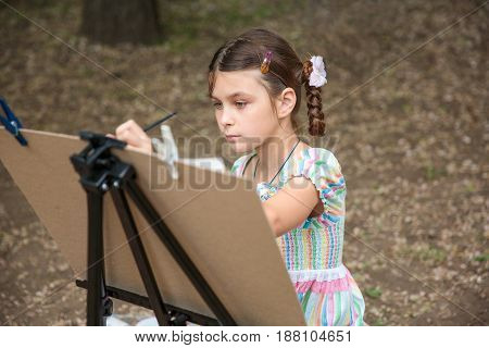 girl painting on easel in the park