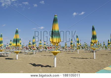 beache umbrellas with beach chairs at the end of the summer season
