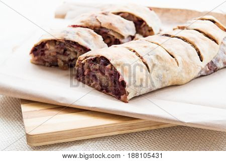 Apple strudel with raisins and cherries on cutting board