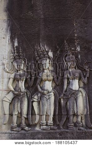 Three female figures carved in Angkor Wat Temple Cambodia.