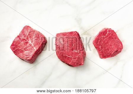 Three slices of raw meat, beef fillet, shot from above on a white marble table with a place for text
