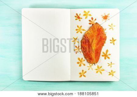 An overhead photo of a notebook with an autumn leaf taped to it on top of simple watercolor drawings of flowers, on a teal background with a place for text