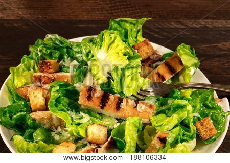 A closeup photo of a plate of chicken Caesar salad with a fork, on a dark rustic background with a place for text