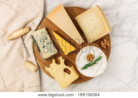 An overhead photo of a selection of cheeses, shot from above on a white marble table, with a wine corkscrew and a cork, and a place for text