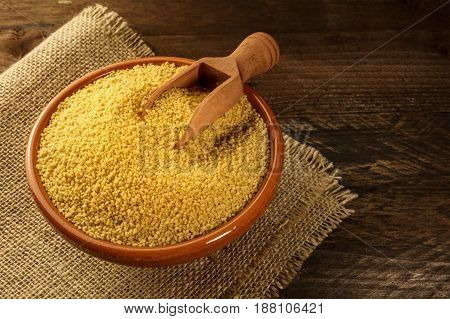 A bowl of raw couscous with a scoop, on dark rustic textures with a place for text