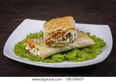 Pita bread wrapped with cottage cheese and vegetables. Close up