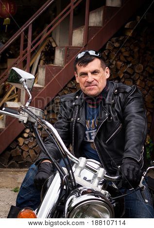 The biker stands near the motorcycle in the courtyard of his house.