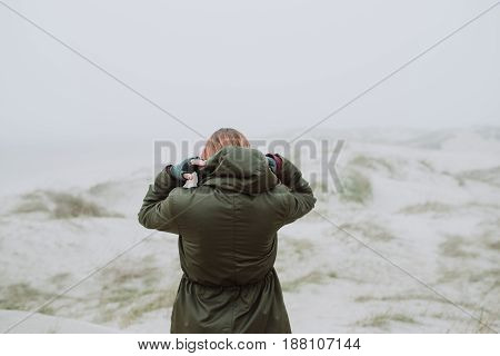 Woman standing on an empty beach in winter time