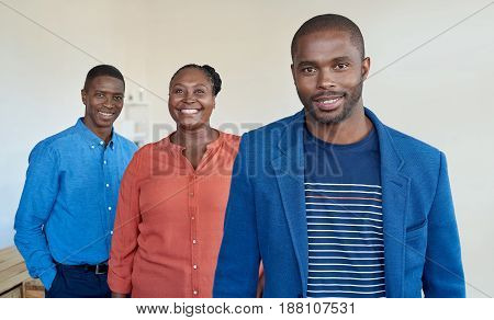 Portrait of three smiling young African business colleagues standing confidently while at work together in a large modern office