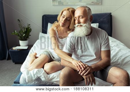Tender Mature Couple Embracing And Relaxing On Bed At Home