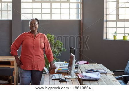 Portrait of a confident young African businesswoman smiling while standing alone by her workstation in a modern office