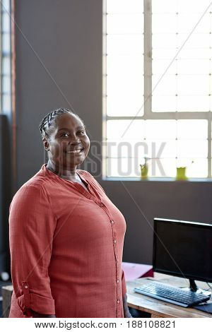 Portrait of a casually dressed young African businesswoman smiling while standing alone by her workstation in a modern office