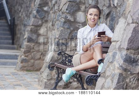 Youth Lifestyle Concepts. Happy Smiling Caucasian Brunette Woman With Headphones Relaxing on Bench and Chatting on Smartphone. Horizontal Image