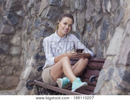 Youth Lifestyle Concepts and Ideas. Smiling Caucasian Brunette Woman With Headphones Relaxing on Bench and Chatting on Cellphone Outdoors. Horizontal Image Orientation