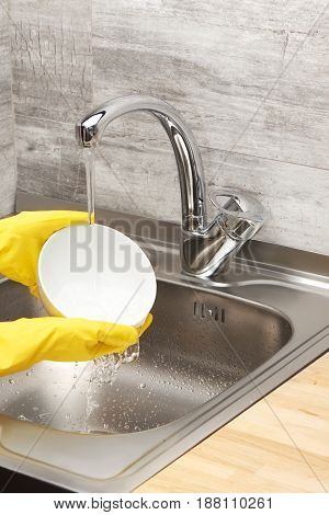 Hands In Yellow Gloves Washing White Bowl Under Tap Water