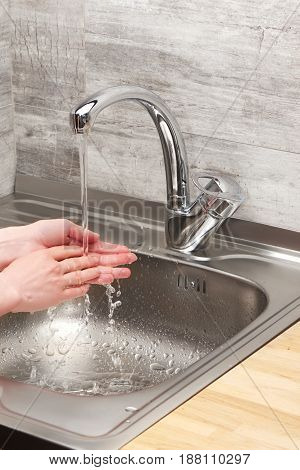 Female Hands Under Running Tap Water Against Kitchen Sink