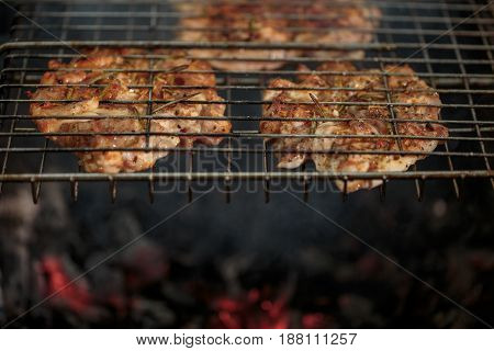 Fresh meat seasoned on the grill outdoors
