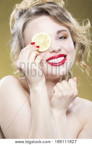 Lemon Fruit Series. Closeup Portrait of Sensual Naked Caucasian Blond Girl Posing with Lemon Slice Against Yellow.Vertical Shot