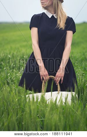 front view close up of woman wearing a black dress and holding in her hands a wicker white bag in a green field of wheat