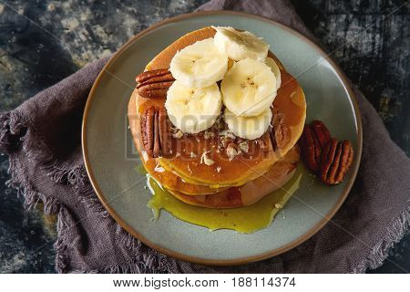 American Pancakes On A Plate With Banana And Nuts, Sweet Sauce.