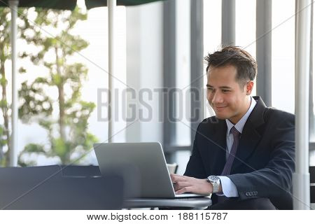 Young Asian businessman working with laptop computer at outdoor cafe