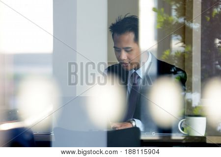 Young Asian businessman working with laptop computer in coffee shop