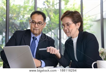 Businessman and businesswoman discussing and working together during a meeting in office