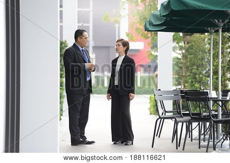 Businessman and businesswoman discussing and working together during a meeting outside office