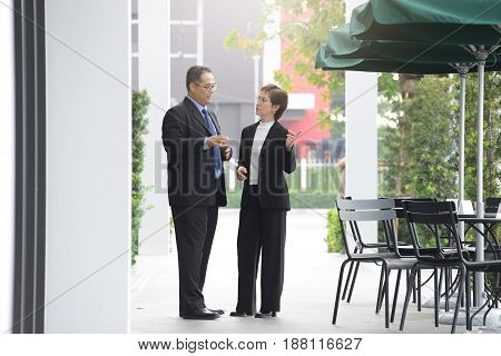 Businessman and businesswoman discussing and working together outside office