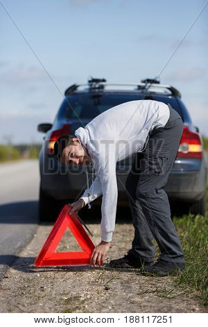 Photo of young man putting red triangle on road near broken car during day
