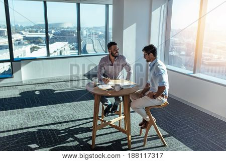 Business partners in happy mood discussing work. Two men sitting at a table in office in a highrise building.