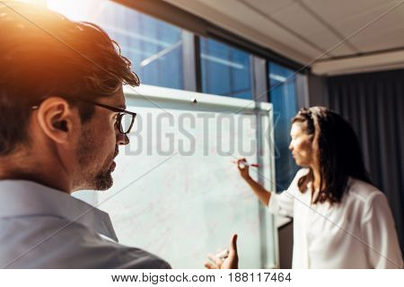 Colleagues discussing business plans in office. Businesswoman presenting ideas on a whiteboard while businessman discussing with her.