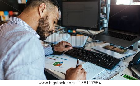 Businessman sitting at his table analyzing data and charts. Man working at his office desk with computers notes and presentation papers.