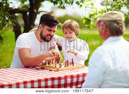 happy family of three generation of men playing chess in spring garden