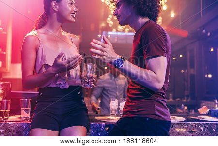 Shot of young man and woman enjoying a party. Couple talking at a nightclub.