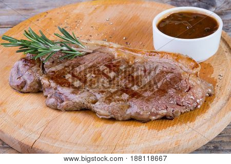 Beef steak with sauce served on a wooden board