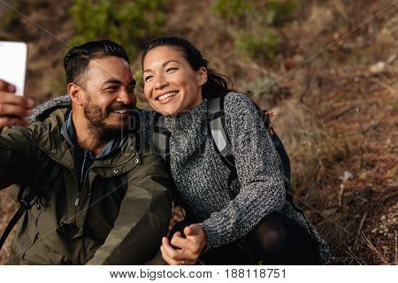 Couple Sitting On Mountain Trail Taking Selfie