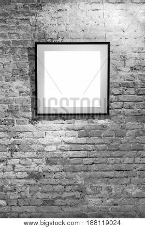 Empty frame on light brick wall. Blank space poster or art frame waiting to be filled. Square Black Frame Mock-Up.