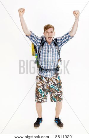 Hiker man with backpack rising arms in victory sign on the white background