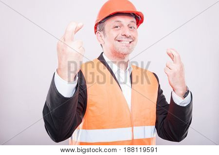 Engineer Smiling Wearing Hardhat Making Fingers Crossed Gesture