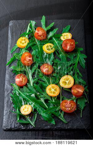Fresh arugula salad with kumquat and tomato cherry on slate plate. Healthy food. Diet